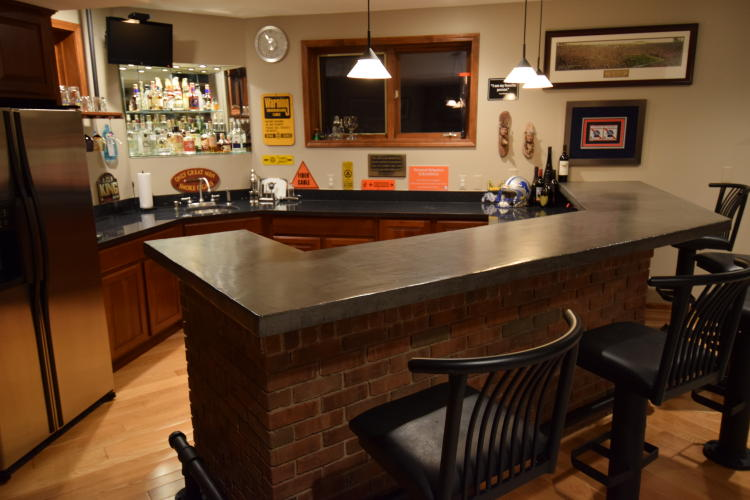 Gray Decorative Concrete Overlay of Wood Bar Countertop In Finished Basement After Clear Gloss Epoxy Sealer And Matte Wax