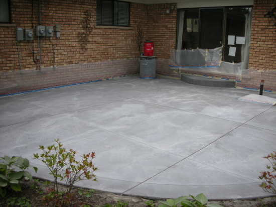 Backyard Concrete Patio Resurfaced With Saw-Cut Pattern Prior To Spray-Texture Decorative Cement Overlay