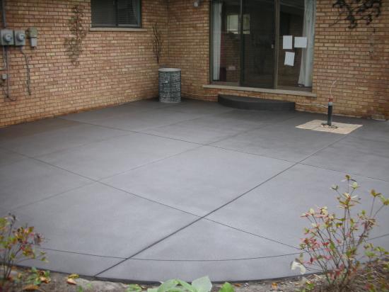 Charcoal Gray Spray-Texture Cement Overlay Of Backyard Concrete Patio With Clear Polyurea Sealer