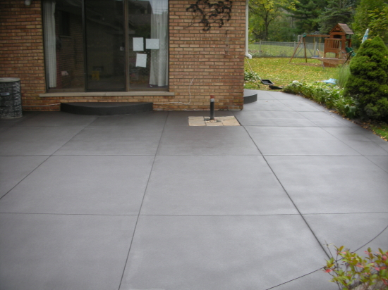 Charcoal Gray Spray-Texture Cement Overlay Of Backyard Concrete Patio With Saw-Cut Design And Clear Polyurea Sealer