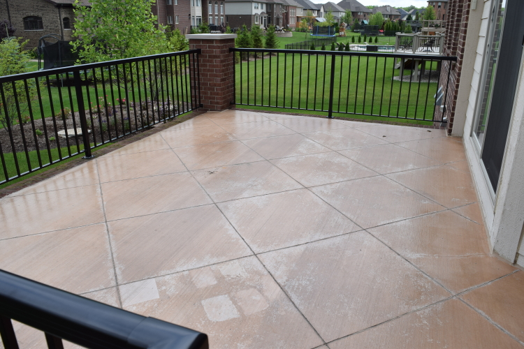 Elevated Backyard Decorative Concrete Terrace With Test Samples Of Chemical Stripper To Remove Sealer