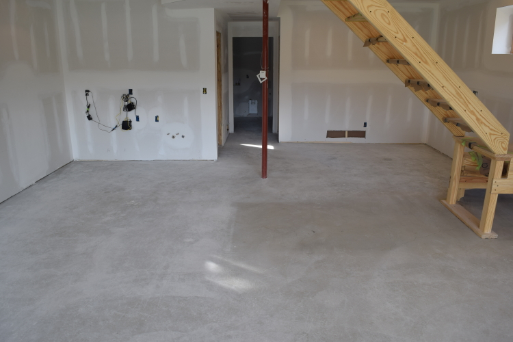 Unfinished Basement Concrete Floor With Drywall Dust Before Cleaning