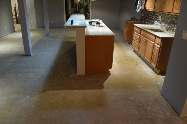 Finished Basement, Kitchen Concrete Floor With Yellow Tile Adhesive Before Grinding And Acid-Staining
