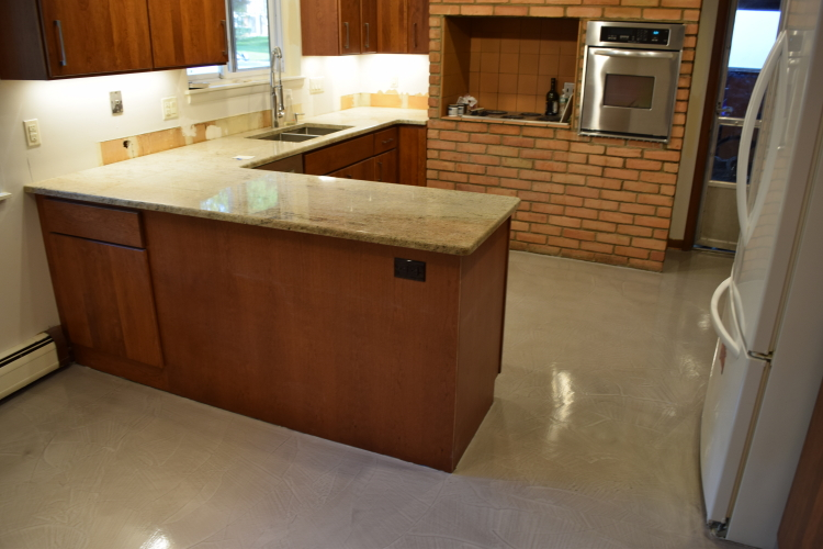 Kitchen And Dinette Concrete Floor Resurfaced With Gray Decorative Cement Overlay And Sealed With Clear Epoxy Coating