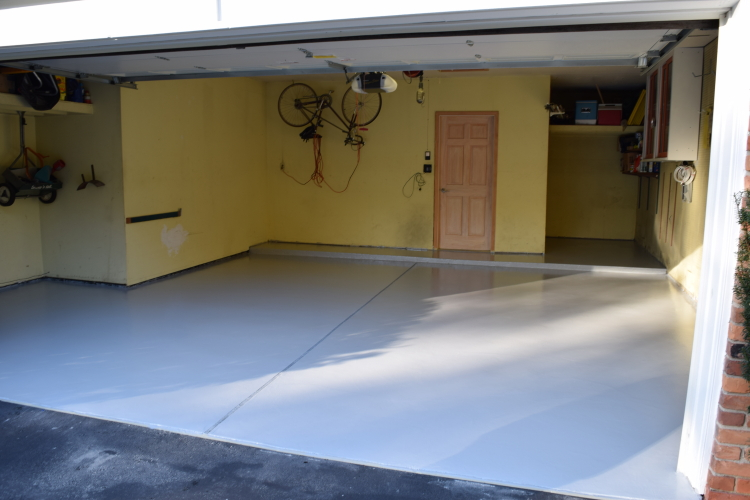 Two-Car Garage Concrete Floor After Making Repairs, Resurfacing And Applying New Gray Polyurea Coating