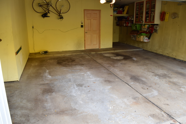 Closeup Of Dirty, Damaged Two-Car Garage Concrete Floor Before Grinding, Repairs, Installing Cement Overlay And Applying Colored Polyurea Coating