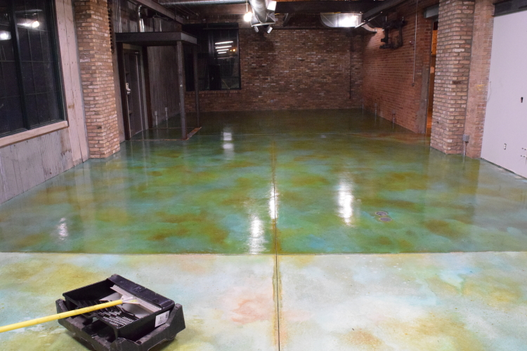 Blue Acid-Stained Concrete Floor With Brown Accenting During Application of Clear Sealer