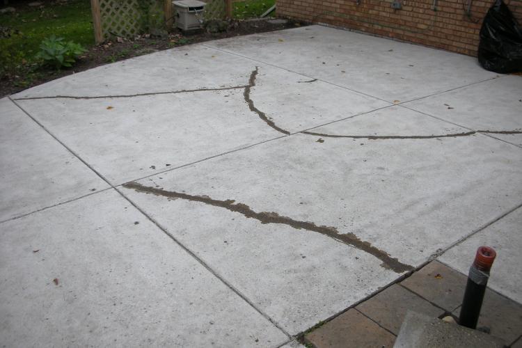 Surface Preparation of Backyard Concrete Patio Including Crack Repair Before Installing Decorative Concrete Overlay