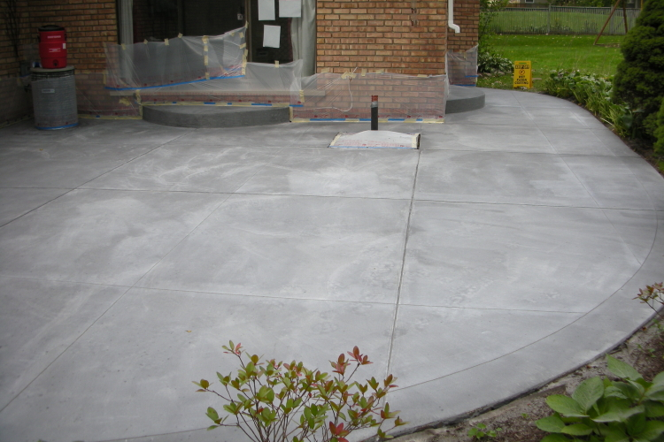Backyard Concrete Patio Resurfaced And Saw-Cut Prior To Spray-Texture Decorative Cement Overlay