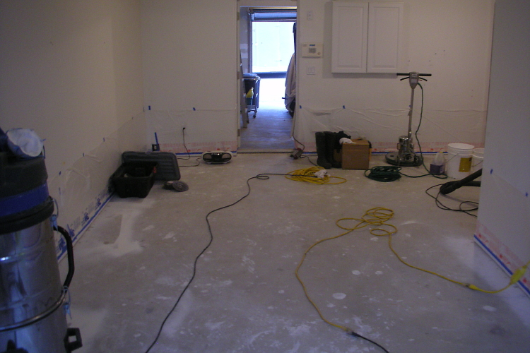 Basement Concrete Floor Covered With Paint And Drywall Mud Before Cleaning And Acid-Staining