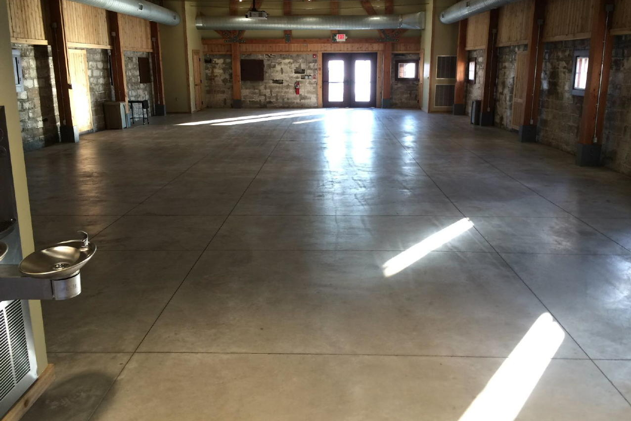 Unsealed, Discolored Museum Concrete Floor Before Cleaning And Coating With Clear Polyurea Sealer