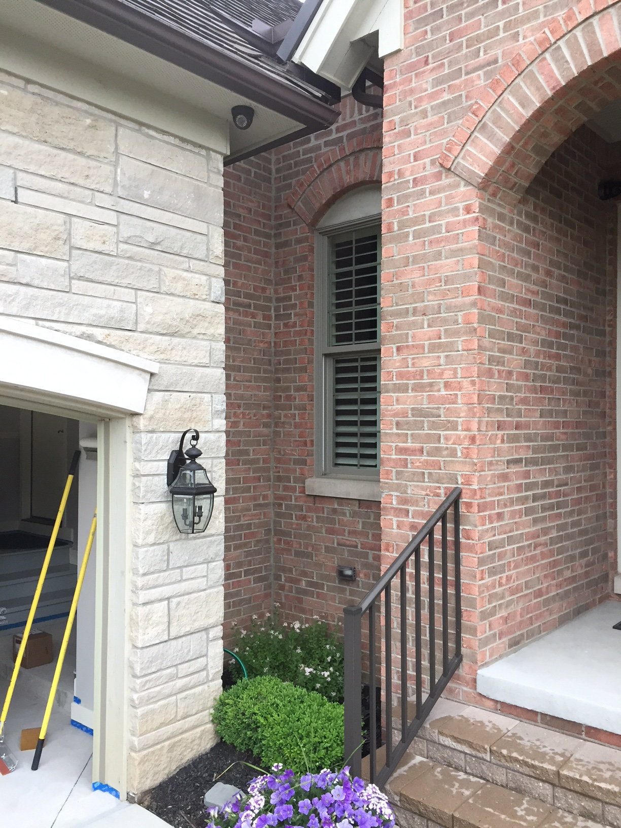 Poor home design allows rainwater from this roof to accumulate in this cubbyhole between the house and garage where it cannot evaporate, forcing it to drain under the driveway and garage and cause a concrete moisture problem.
