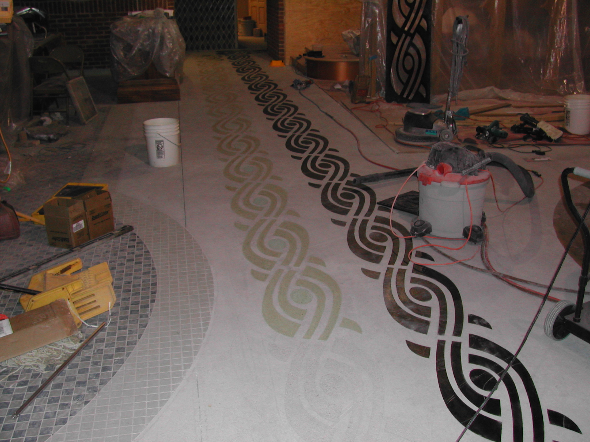A border pattern is transferred to the concrete floor in a bar using black spray lacquer and then those areas are engraved out and acid-stained.