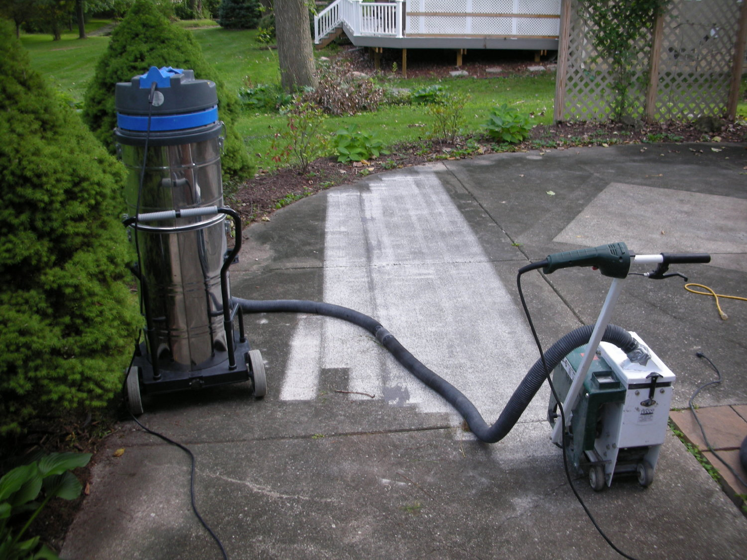 Shot-blasting was required to clean this concrete patio (before resurfacing with an overlay) because of the rough texture and longstanding dirt and discoloration.