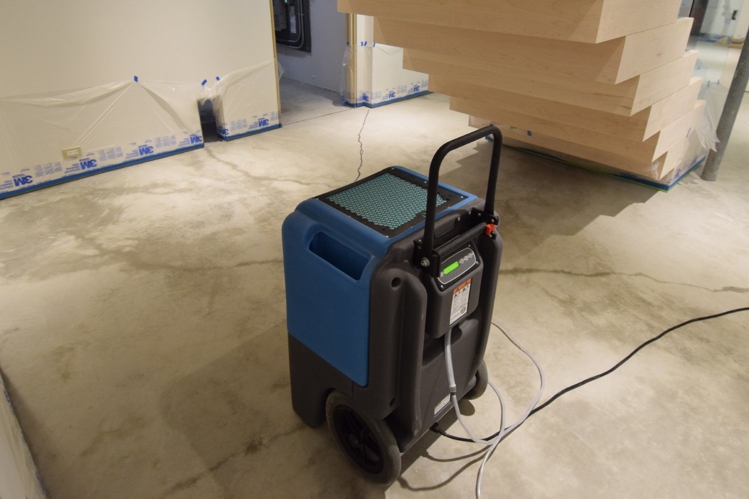 This is the LGR 700XLi from Dri-Eaz. Used in conjunction with a blower fan, this dehumidifier will dry out the dampness left from cleaning this basement concrete floor in time for it to be acid-stained the next day.