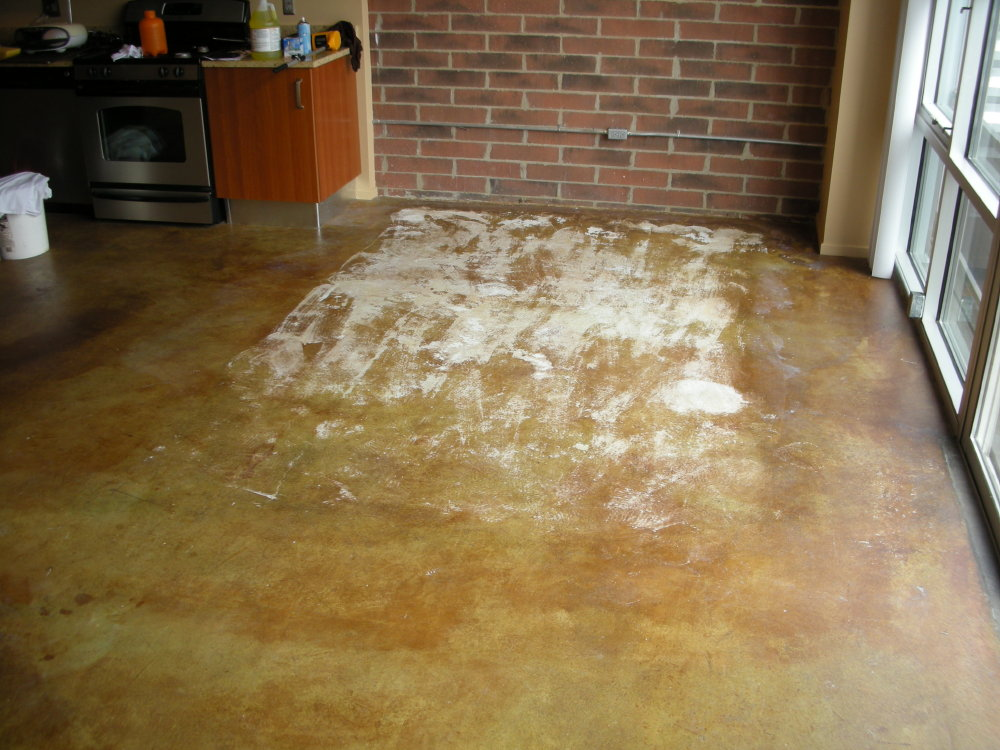An area rug with a tacky bottom was placed under a dining table on this acid-stained concrete floor.  A year later it could not be removed without taking the concrete sealer and stain with it.