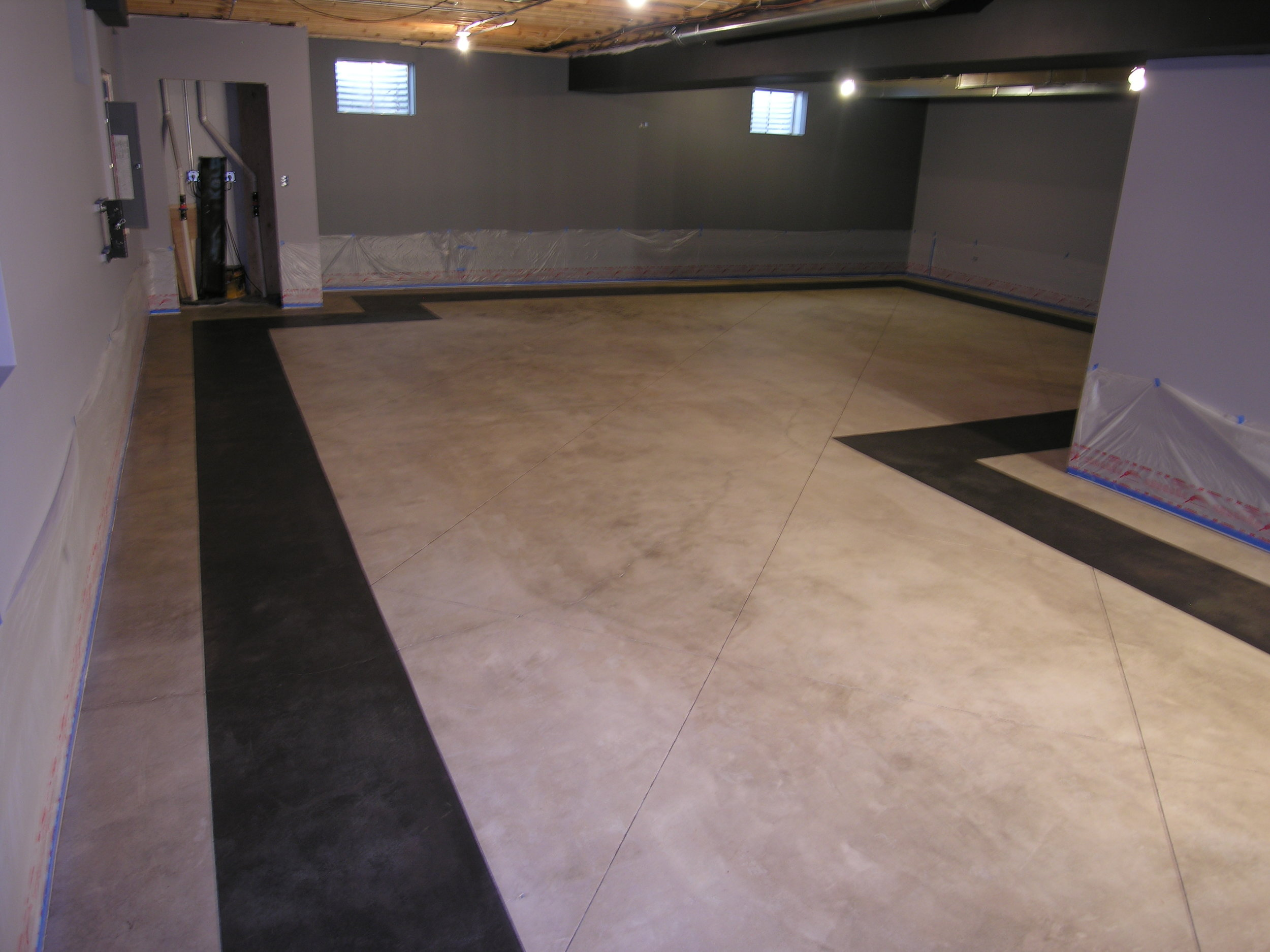 Finished Basement Acid-Stained Concrete Floor With Saw-Cut Black Border Before Applying Clear Sealer