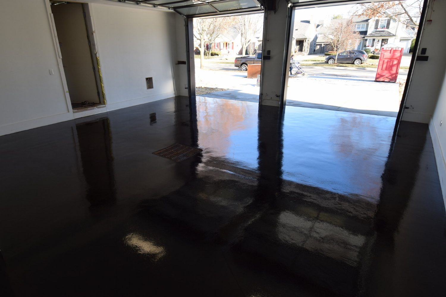 Custom Home Garage Concrete Floor Acid-Stained Black And Coated With Clear Gloss Polyurea Sealer