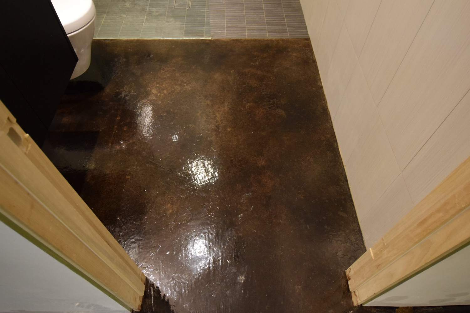 Black Acid-Stained Basement Bathroom Concrete Floor After Removing Paint Drip Blemishes By Faux Finishing