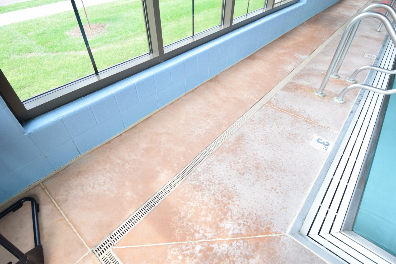 Closeup View Of Discolored, Indoor Concrete Pool Deck Before Resurfacing With Spray-Texture Decorative Cement Overlay