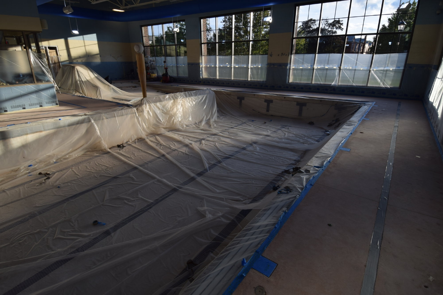 Commercial Indoor Concrete Pool Deck Masked Off With Plastic To Protect Adjacent Surfaces During Spray-Texture Decorative Cement Overlay