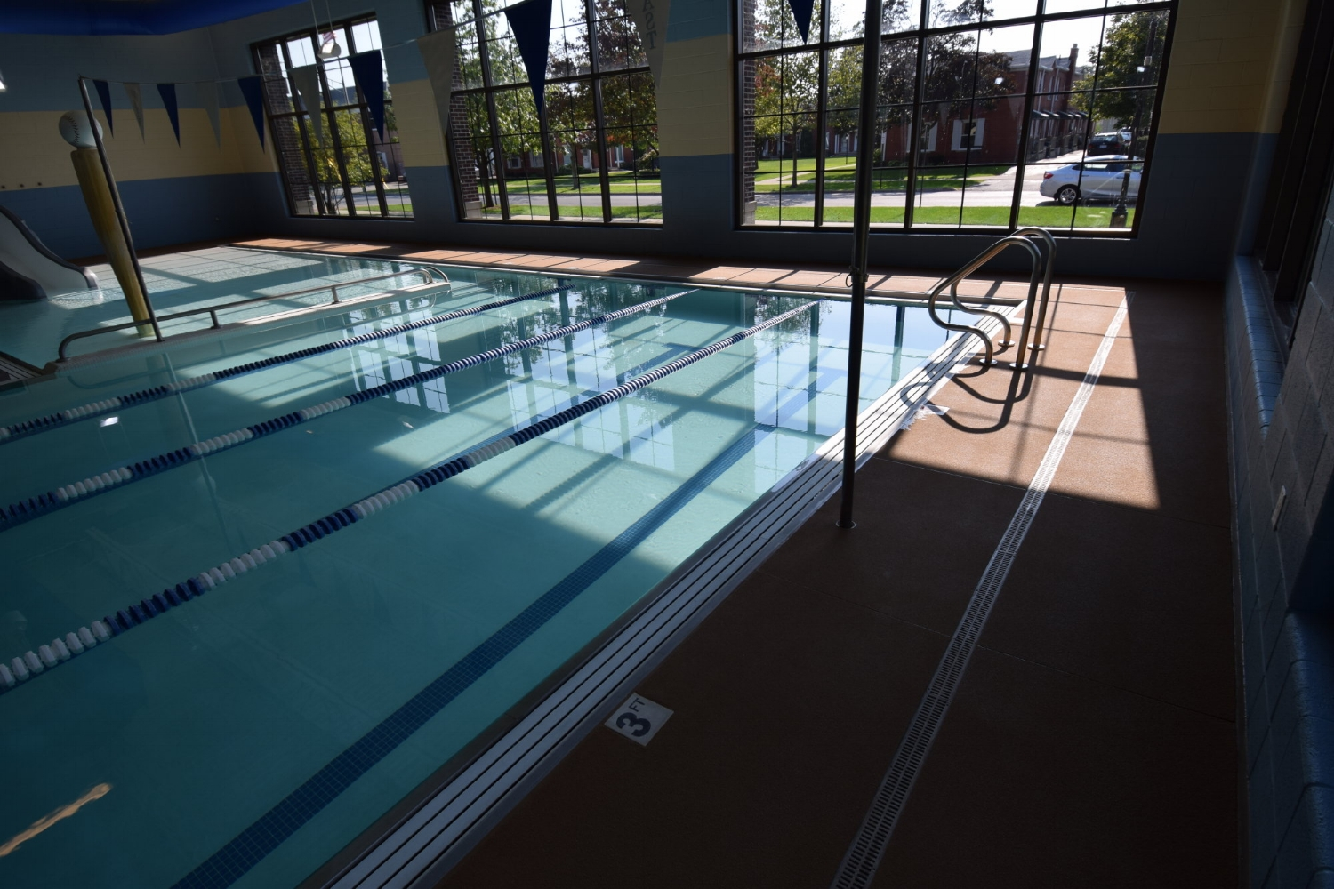 Commercial, Indoor Concrete Pool Deck After Resurfacing With Integrally-Colored, Spray-Texture, Decorative Cement Overlay And Removing Masking Plastic
