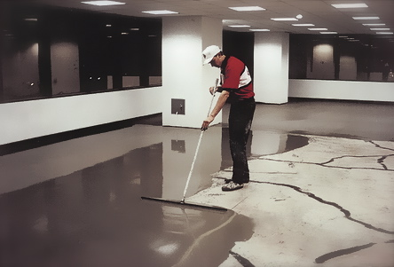 Ardex SDT is one of the best self-leveling overlays on the market.  On a large flooring project, it is usually pumped through a hose, rather than poured from a plastic mixing barrel.