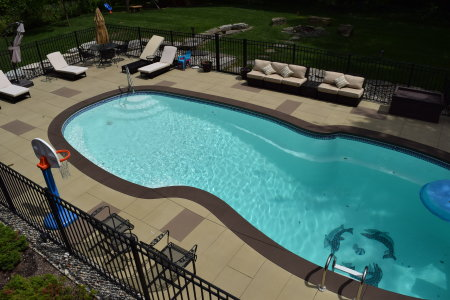 """Integrally-colored, """"spray-texture"""" concrete overlays create a perfect decorative finish on plain gray outdoor pool decks. Spray texture overlays look great, have ideal slip-resistance and are easy to clean and maintain."""