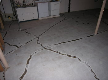 These settlement cracks in a basement concrete floor were repaired using epoxy.  After drying overnight, excess material was ground off and an overlay installed.  The cracks did not return.
