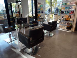"Decorative concrete flooring with a high performance, chemical-resistant clear sealer is a common choice for hair salons.  The flooring in this particular salon is a 3/8"" self-leveling cement overlay colored with brown concrete dye."