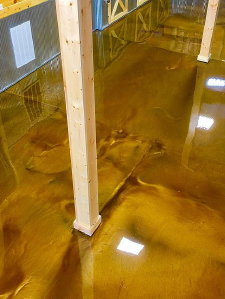By contrast, this metallic epoxy floor was installed by another contractor at a Michigan DNR office in 2017, using the same colors.  Pigment pooling in low areas created an unnatural, unsightly and synthetic look.