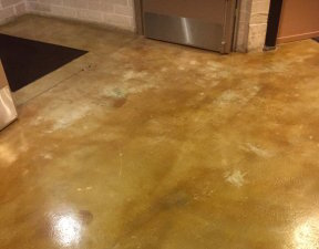 This condominium concrete floor was acid-stained by a commercial cleaning contractor. In their haste to get the project done, they didn't remove all the carpet glue, and the remaining residue left bare spots across the floor.