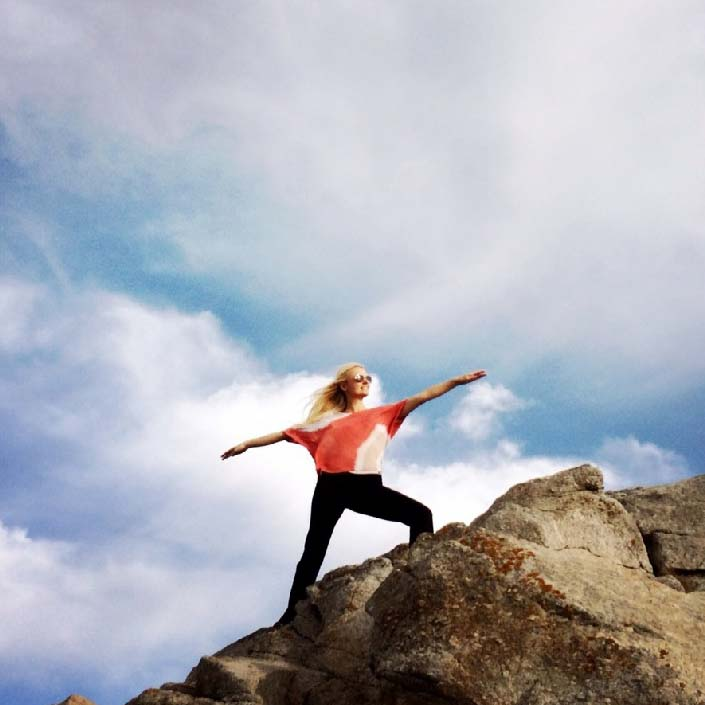 Yogini in Warrior Pose on rocky cliff
