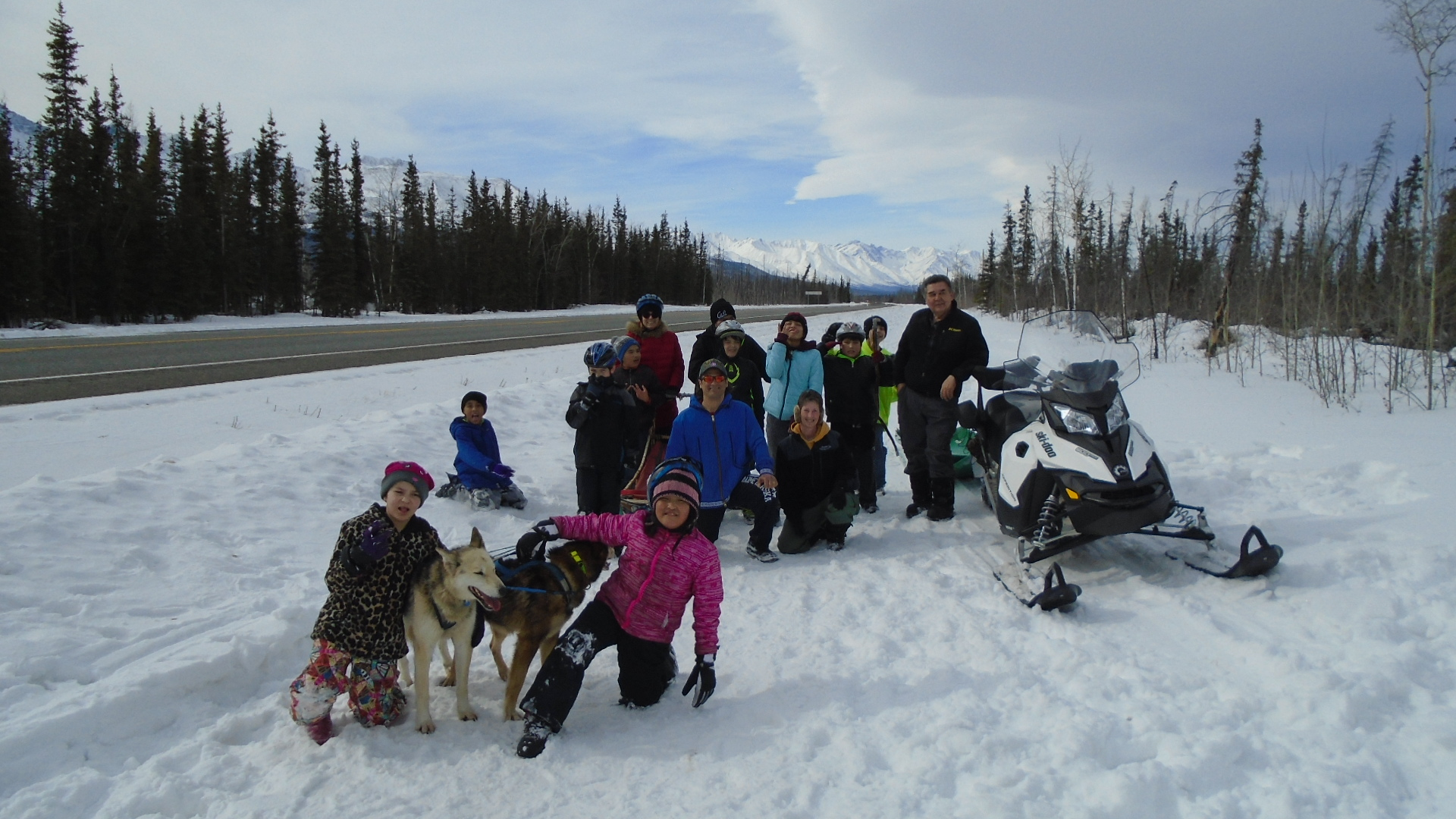 The Tanacross School class rests with Musher Teacher Leonard Sanford and his dogs.