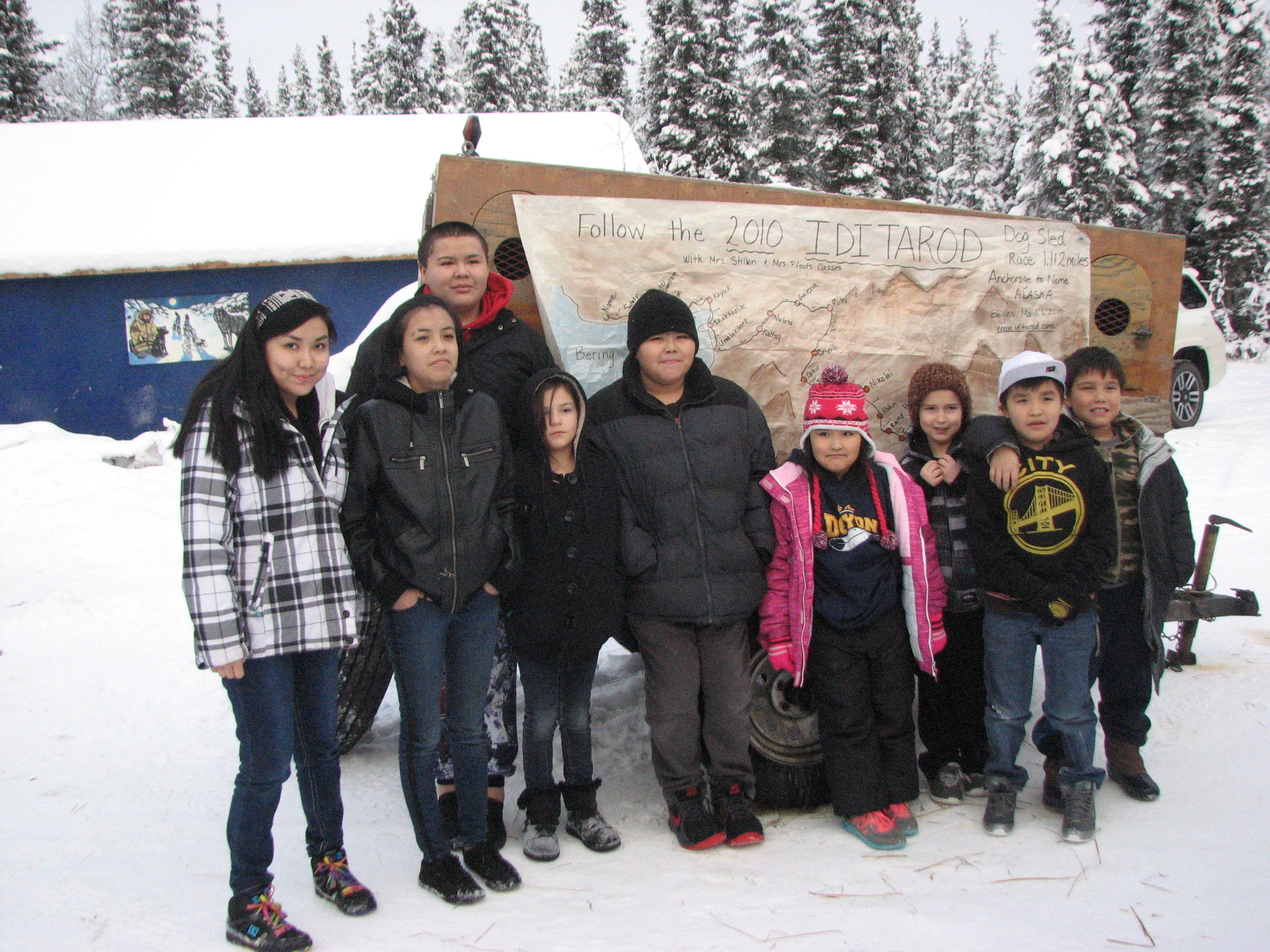 Tanacross students and Leonard Sanford stand by Iditarod map at Hugh Neff's Kennel.