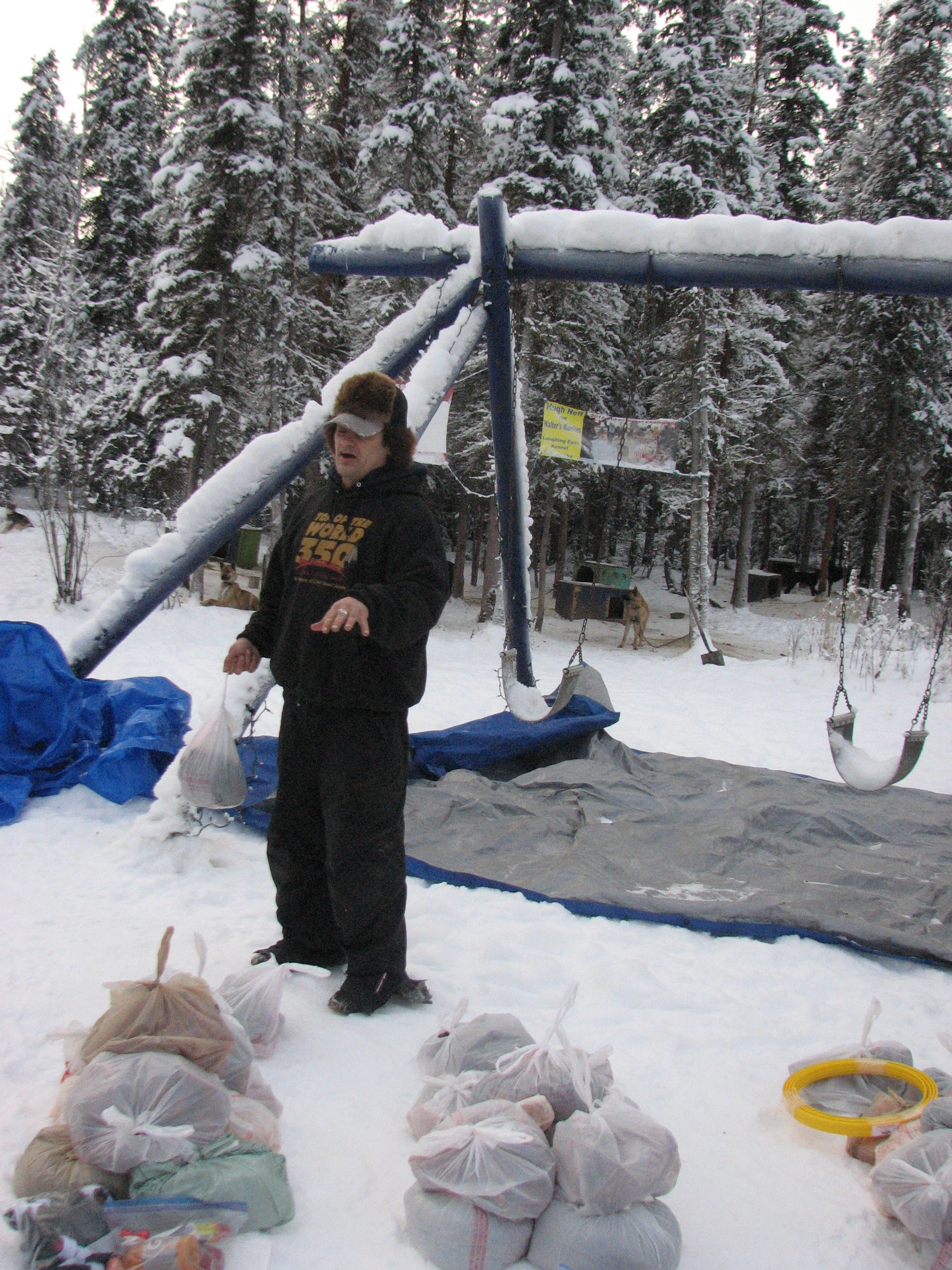Hugh Neff explains the Iditarod checkpoint bags at his kennel.