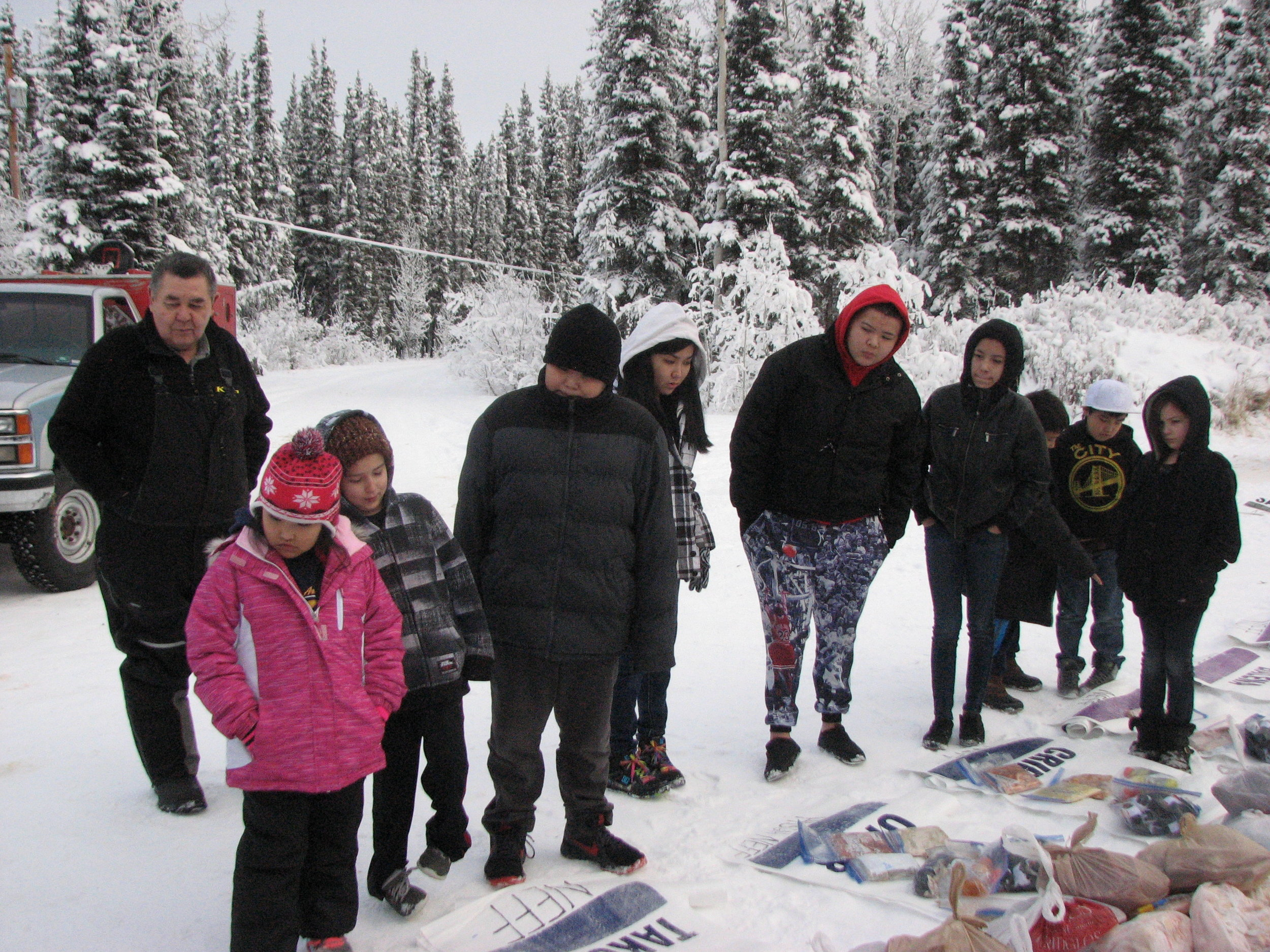 Tanacross students and Leonard Sanford learn more about the Iditarod checkpoint bags.