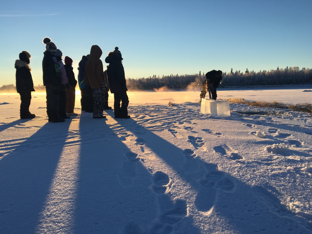 Huslia JHS students observe how to cut holes in ice to set fish net.