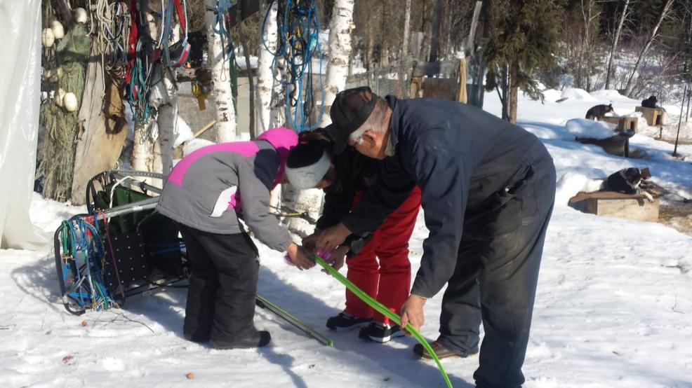 Allakaket School students learn from Musher Steven Bergman how to change sled runner.