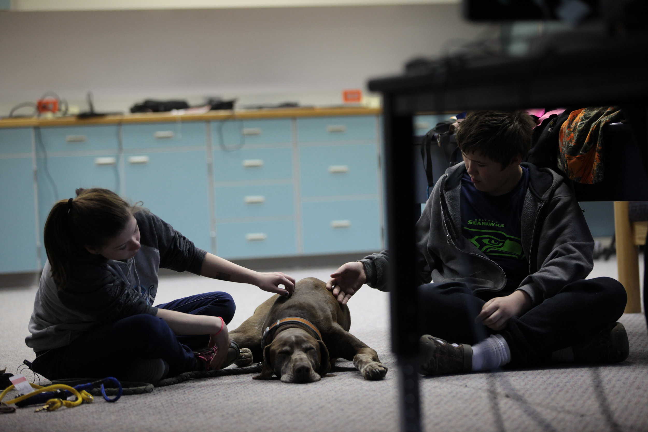 Tok students with dog in classroom.