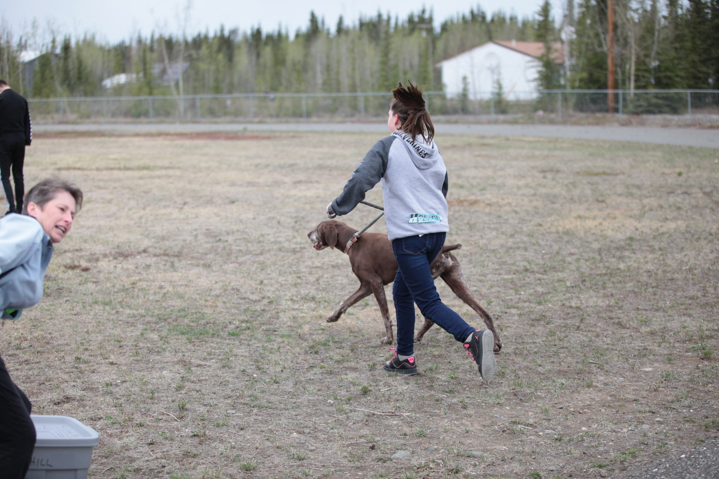 Tok student exercising with dog.