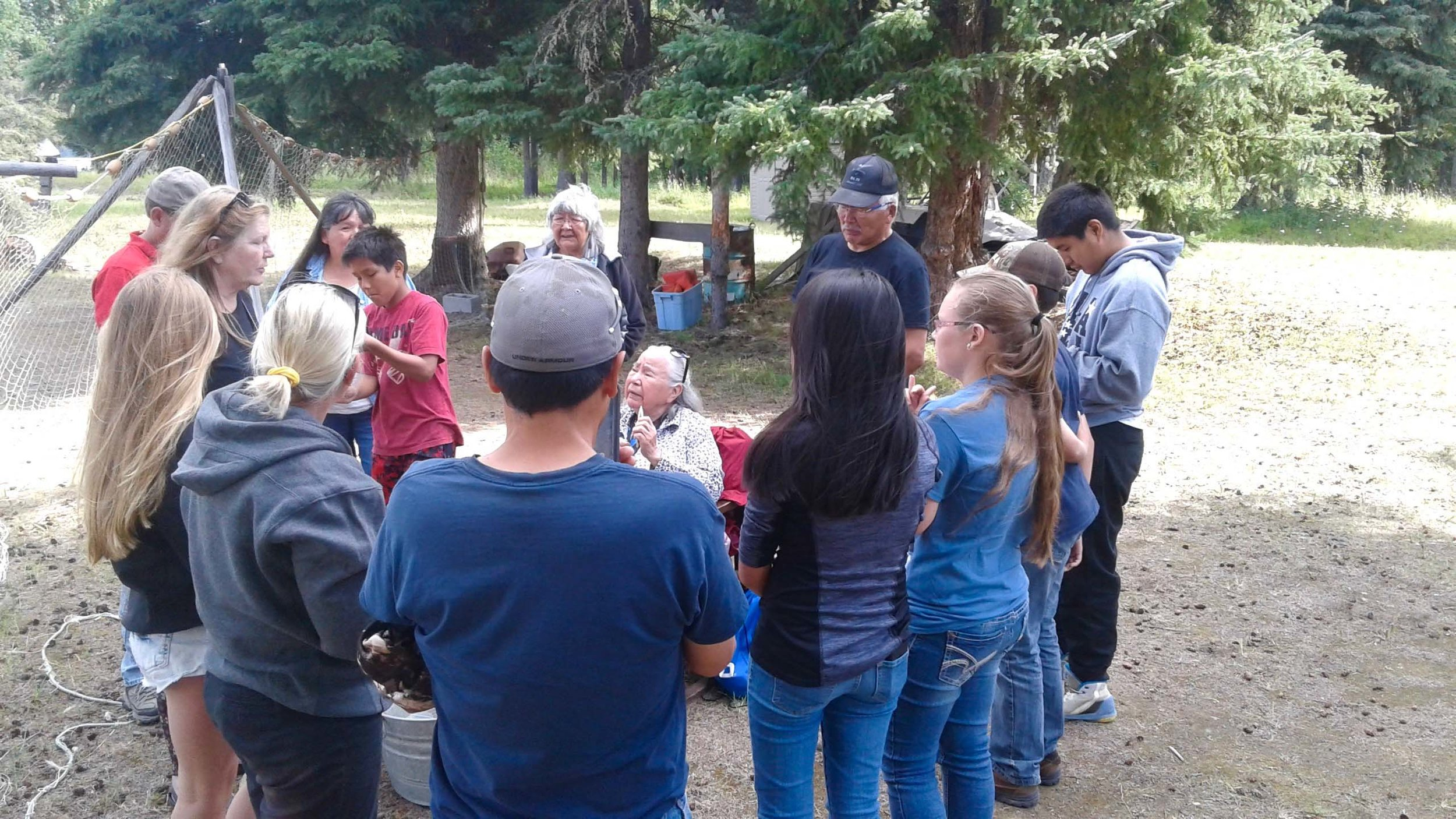 An Elder shows A-CHILL students, dog mushers, and teachers how to mend fish net.