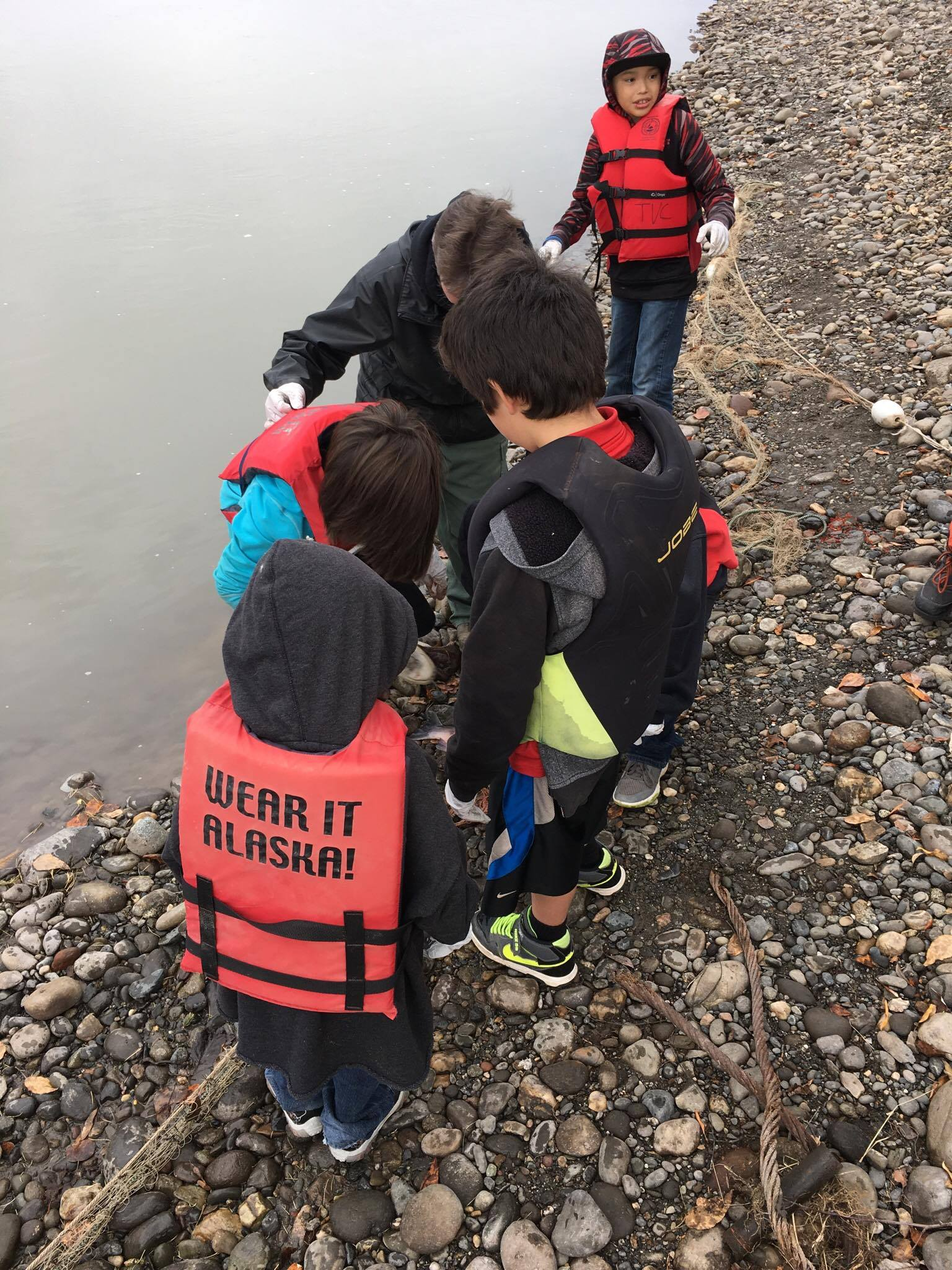 Students leaning in to check fish net.