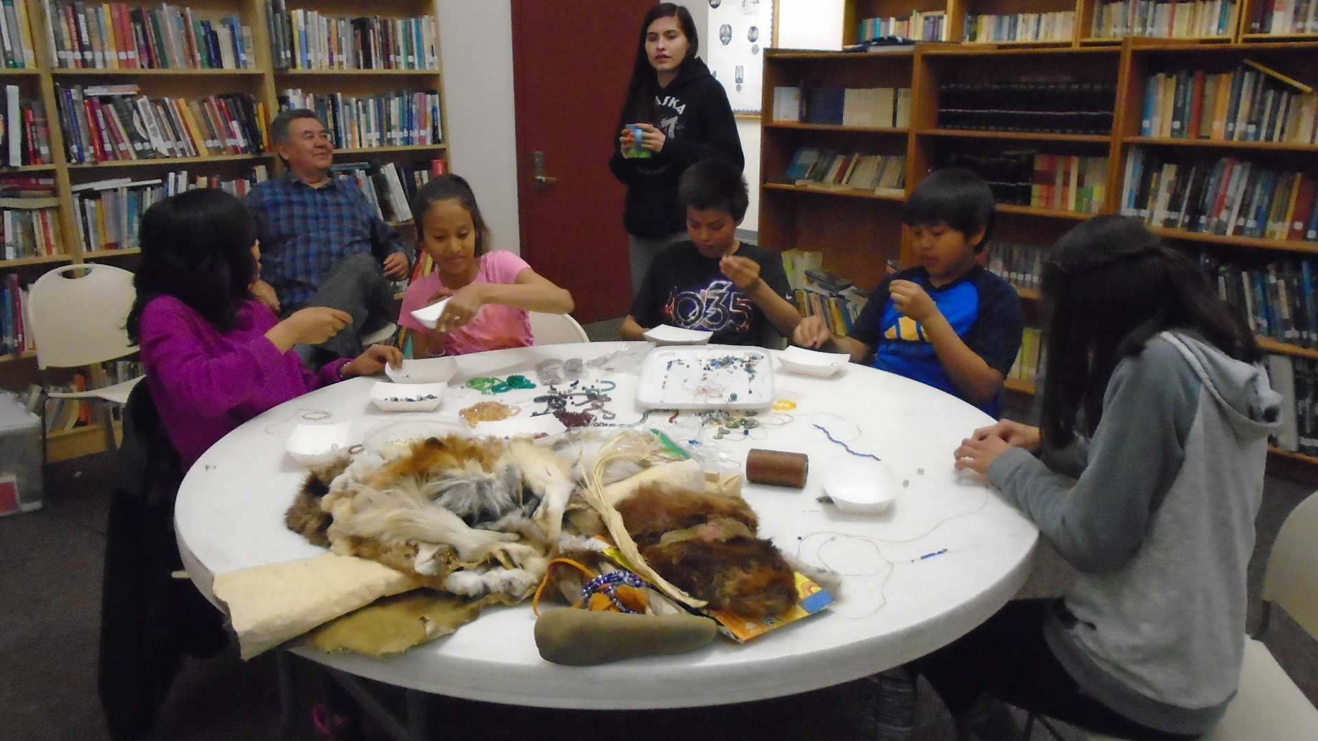 Students learn to bead with Amanda Attla.