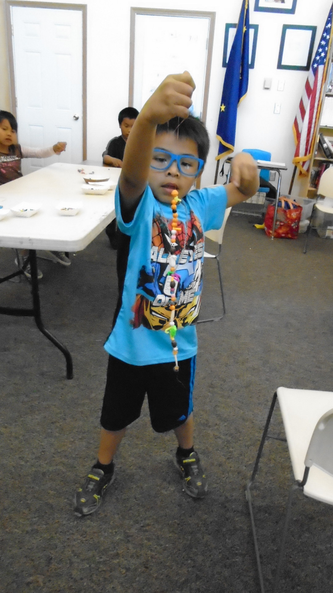 A student shows off his result of the beading instruction.
