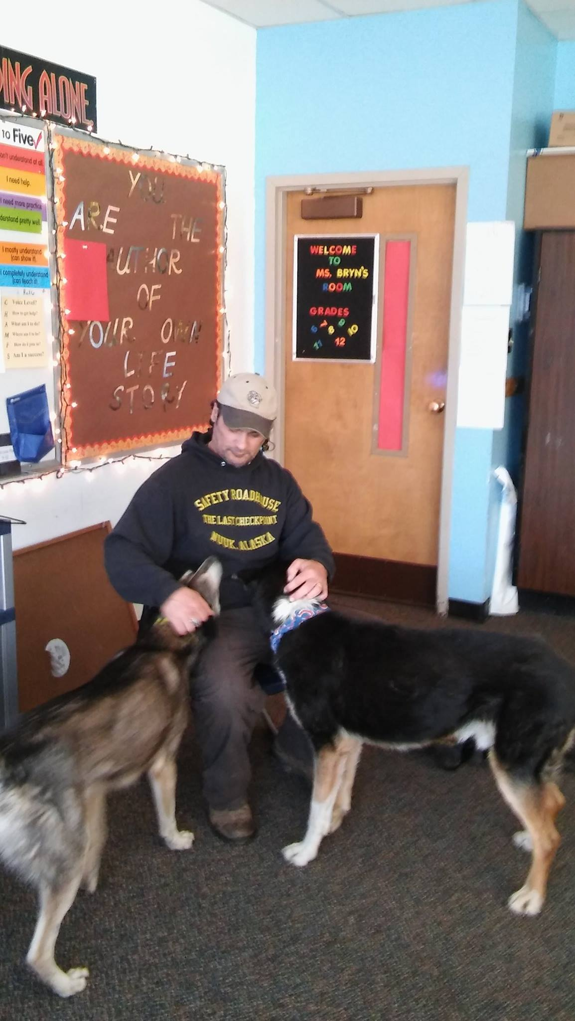 Dog Musher Teacher Hugh Bifelt with dogs and students in classroom.