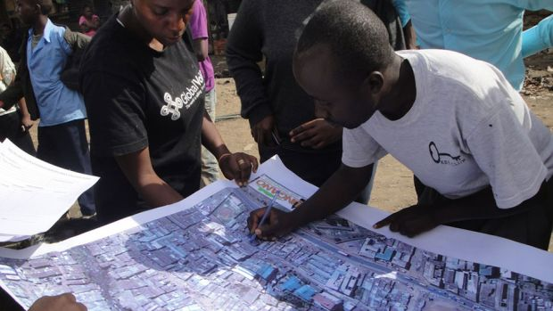 Surveying an aerial map of food safety threats in Mathare, an informal settlement in Nairobi Kenya (photo: Sohel Ahmed, DPU, UCL).