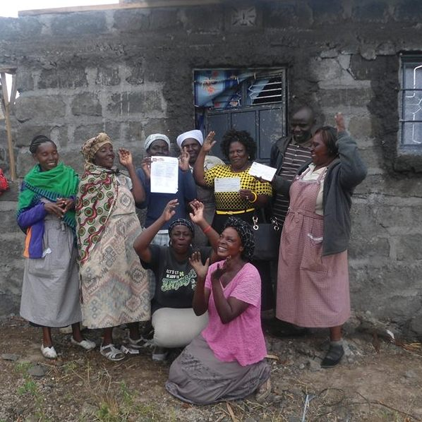 Members of the Muungano Wa Wanavijiji Nakuru West Network, receive a cheque from AMT's Board member Anastacia Wairimu for the Shikamoo D housing project