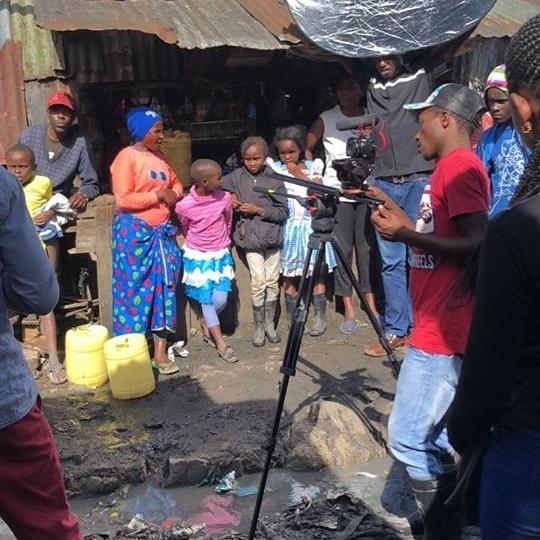 Julius Obi from Muungano's KYC.TV team preparing to film a scene in Mukuru, Nairobi.