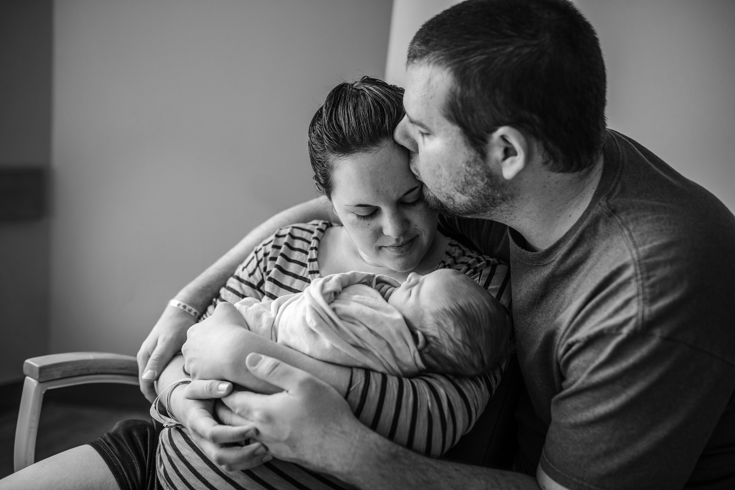 Black and white photo of family kissing after baby's epidural birth at a hospital in Jacksonville, Florida.